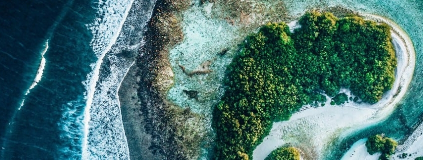Ariel picture of small rain forested isand surrounded by coral and blue ocean