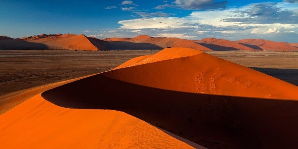 Huge red and orange sand dune rising above a flat salt pan in Namibia's Namib-Naukluft National Park