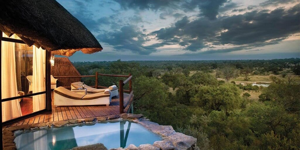 view from luxury safari room over terrace with pool to savannah below