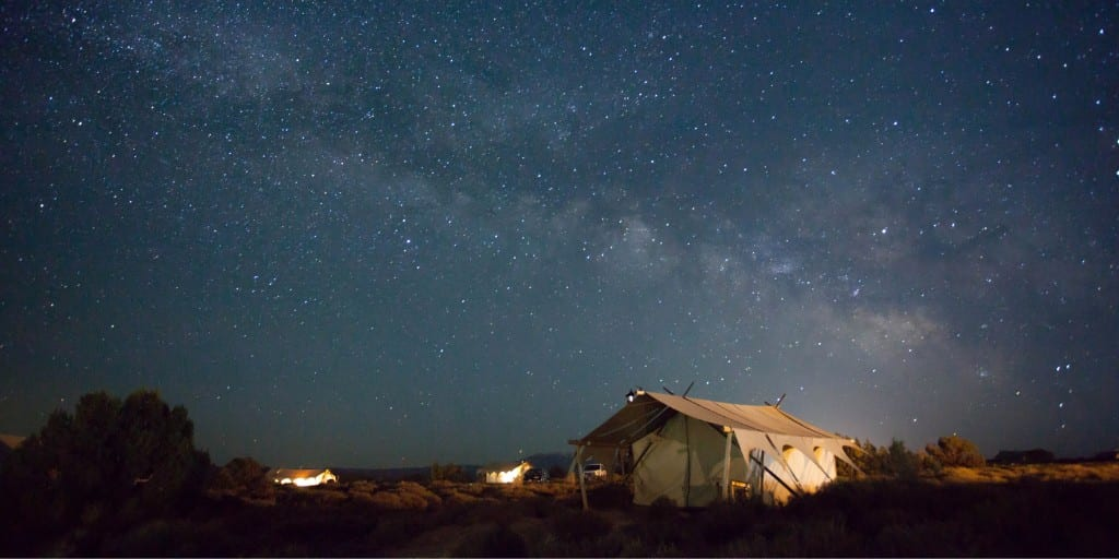 safari tents on horizon under large, night time starry sky
