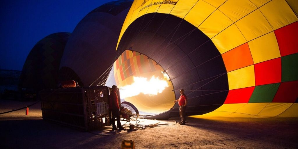 hot air balloon being blown up at dusk for a safari
