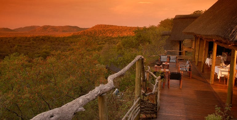 safari lodge exterior at sunset, with view over green mountains