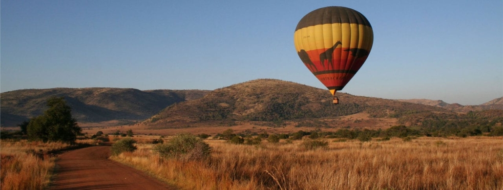 Low flying hot air balloon over bushland in blue sky