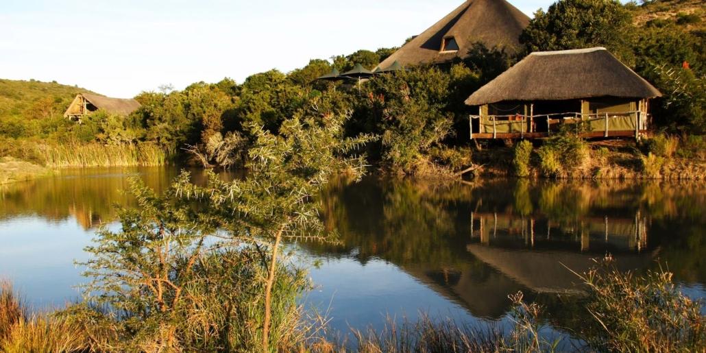 Exterior shot of thatched lodge at Shamwari, view across the lake