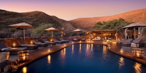 pool at luxury safari loge with mountains in pink sunset behind